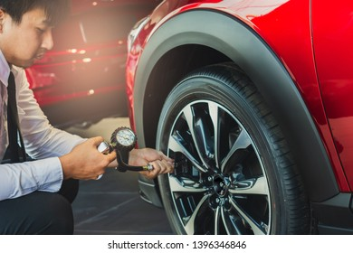 Asian man car inspection Measure quantity Inflated Rubber tires car.Close up hand holding machine Inflated pressure gauge for car tyre pressure measurement for automotive, automobile image