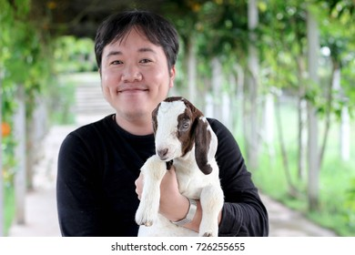 Asian man carry a baby goat in the farm