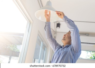 Asian man changing light bulb in coffee shop , installing a fluorescent light bulb