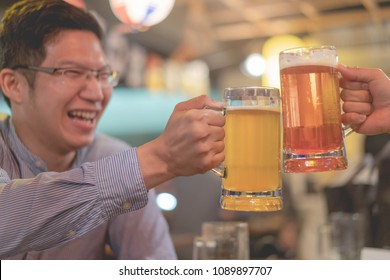 asian man cheering  clinking glasses beer in bar