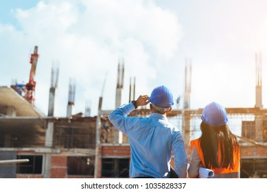 Asian man civil engineer and woman architect wearing blue safety helmet meeting at contruction site.