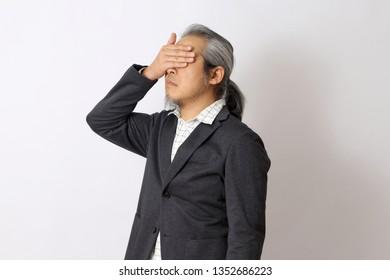 The Asian man closing his eyes.