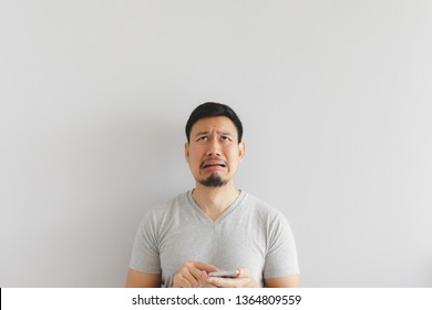 Asian man cry and sad with what show on the smartphone.