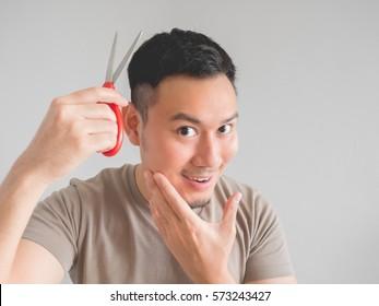 Asian man cut his own hair with clipper and scissor.