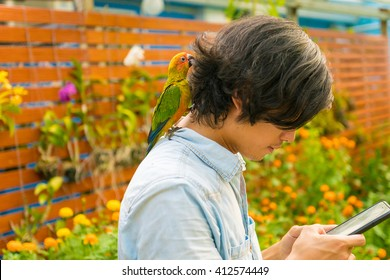 Asian Man with cute parrot sit on the shoulder in garden - side view