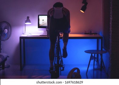 Asian man cycling on the machine trainer he is exercising in the home at night.he play online bike game