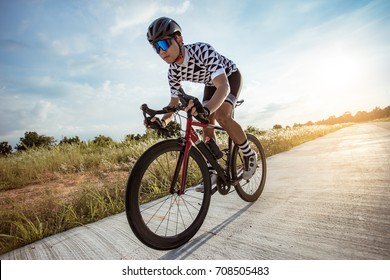 Asian man Cyclist riding a bike on an open road to the sunset in Thailand