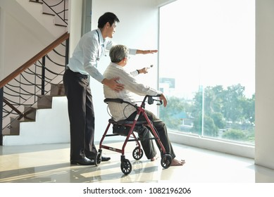 Asian Man Doctor is talking with his Senior male patient in a medical room. Elderly male sitting on wheelchair.  Health care, Paralysis, caregiver, consultant.