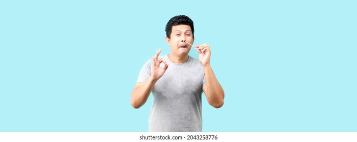 Asian man does a self test for covid 19  on blue background in studio, Coronavirus nasal mucosa test for infection with a medical cotton swab.
