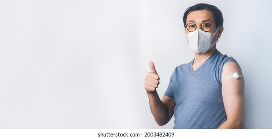 Asian man doing ok sign with fingers and show cotton after make injection Covid-19 or Coronavirus vaccination immunity on his arm
