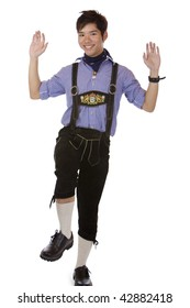 """Asian man dressed in Oktoberfest leather trousers (Lederhose) is doing the traditional Bavarian dance called """"Plattln"""". Isolated on white."""