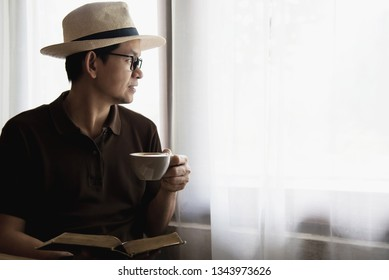 Asian man drink coffee in a modern style coffee shop - people with coffee cup easy lifestyle concept