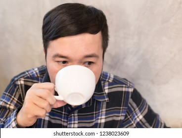 asian man drink hot coffee, he sip and feeling happy in relax time