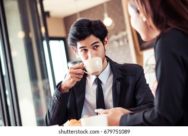 Asian man drinking coffee with co-worker partner in break time