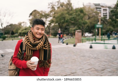 Asian man drinking a cup of coffee.