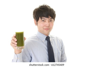 Asian man drinking a glass of vegetable juice.