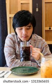 Asian man drinking soda in the restaurant