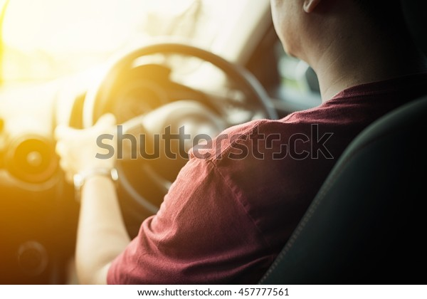 Asian man driving a car. Vintage picture sunlight process warm tone.