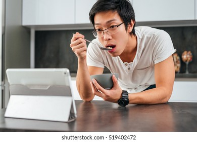 Asian man eating cereal. looking at tablet
