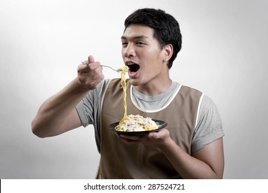 Asian man eatting spaghetti carbonara