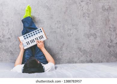 asian man enjoy playing keyboard on bed, music background