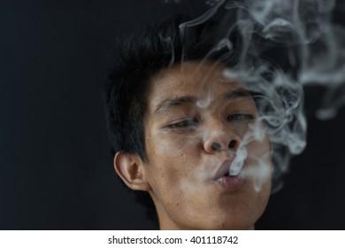 Asian man enjoy smoking cigarette, black background