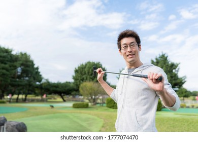 Asian man enjoying putter golf outdoors