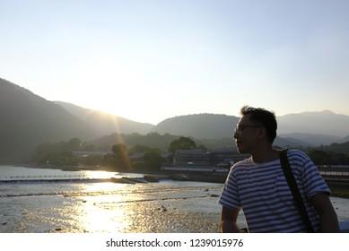 An asian man enjoying the sunset view by Katsura river in Arashiyama, Japan.