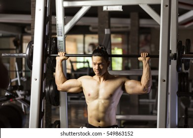 Asian man exercising with barbell in gym.