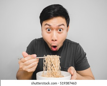 Asian man feel surprise with how delicious instant noodle is.
