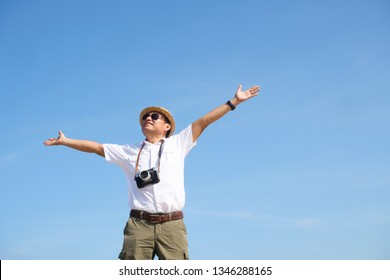 Asian man feeling happy on the beach and blue sky summer time with vintage camera