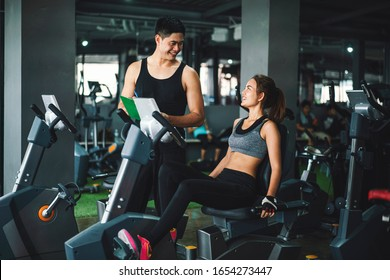 Asian man fitness trainer wearing sportswear helping and supporting his customer workout for bodybuilding in her class, Fitness gym concept