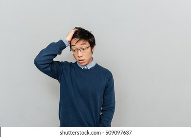 Asian man forgetting something. with glasses. isolated gray background