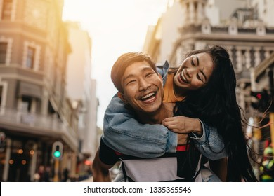 Asian man giving piggyback ride to his girlfriend outdoors in city street. Cheerful couple enjoying themselves in the city.