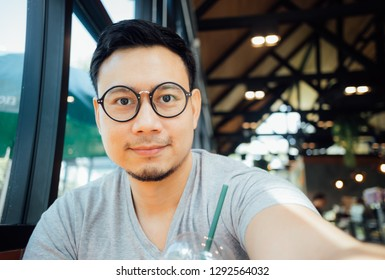 Asian man with glasses selfy himself drink coffee in the cafe.