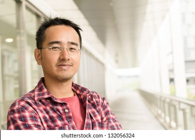Asian man with glasses stand at street, closeup portrait.