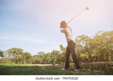 Asian man golf player swinging driver golf club on golf course.