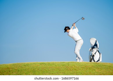 Asian man golfer standing  on slope  with golf bag hitting  golf ball on blue sky background  at golf course , Sport healthy holiday lifestyle  Concept