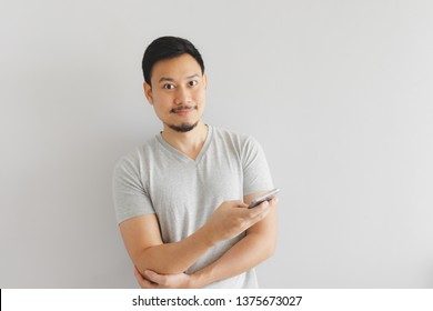 Asian man in grey t-shirt is using the smartphone.