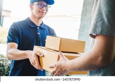 Asian Man hand accepting a delivery boxes from professional deliveryman at home