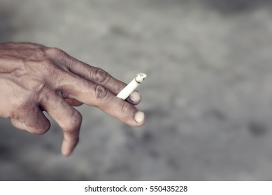 Asian man hand holding a burning cigarette between his two fingers