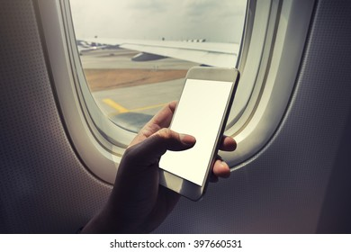 Asian man hand holding i phone 7  on board of airplane near window seat and wing