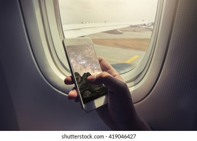Asian man hand holding smart phone and mountain background screen on board of airplane near window seat and wing