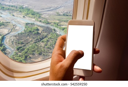 Asian man hand holding smart-phone on board of airplane near window seat and wing with paro valley bhutan background
