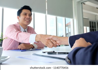 Asian man handshake successfully in job interview at office background, job search, business concept