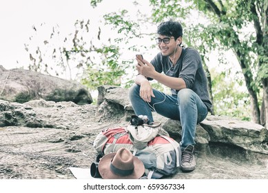 Asian Man Happiness using Smartphone Sitting Alone on Rock in Forest Listening Music Earphones. Having Rest Outdoor. Nature and Modern Technologies and Lifestyle Communications concept