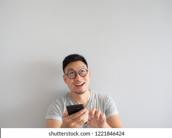 Asian man happy to see what in the smartphone on isolated grey background.