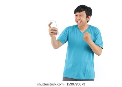 asian man happy smartphone with blue t-shirt. smiling filipino with smartphone