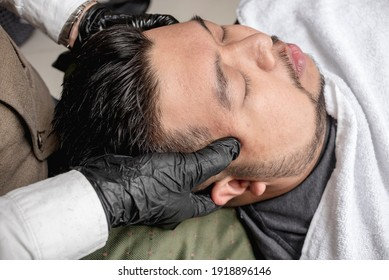An asian man has a complimentary relaxing head massage after a hair cut at a salon or barber shop.