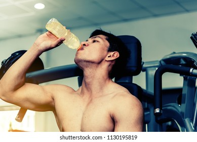 Asian man has muscle exercise in the gym . Athletic handsome man having rest after bodybuilding training drinking electrolyte drink . Healthy sport energy drink concept